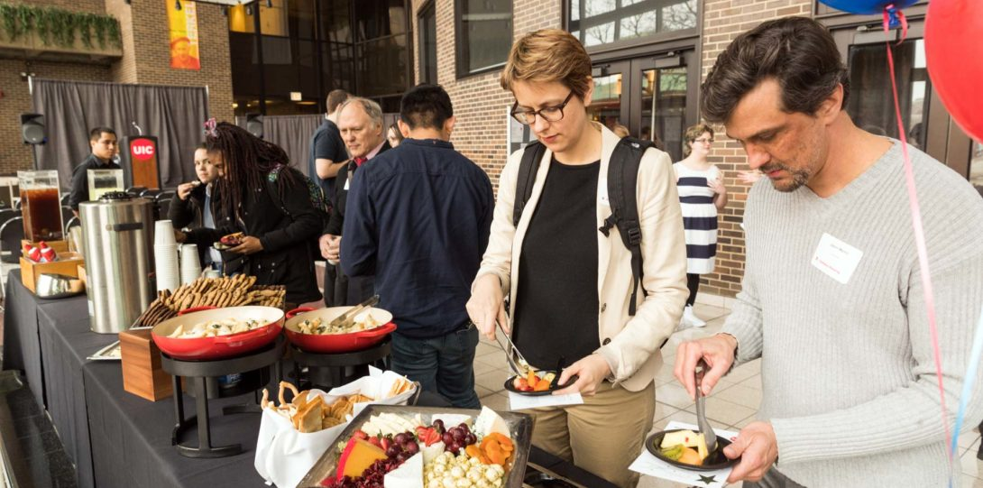 Attendees filling their plates with food.